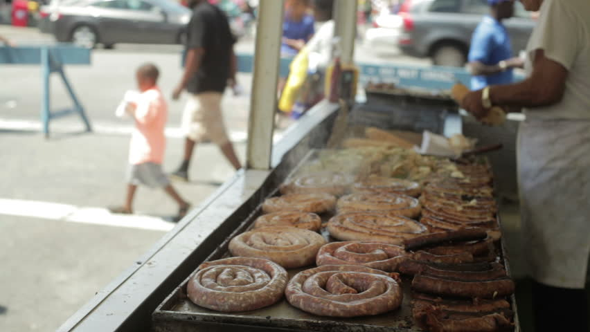 man vending selling and cooking and grilling sausage on a grill outside at a street fair and carnival