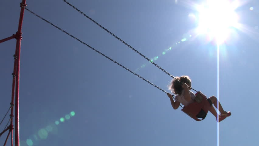 A young girl swings on a swing set. - HD stock footage clip