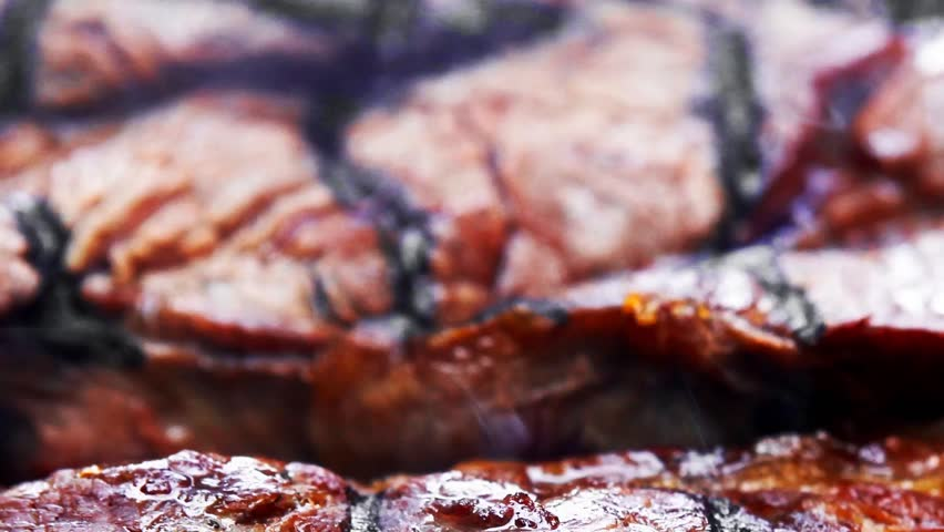 big beef steak on grilling grid over barbecue charcoal 1920x1080 intro motion slow hidef hd