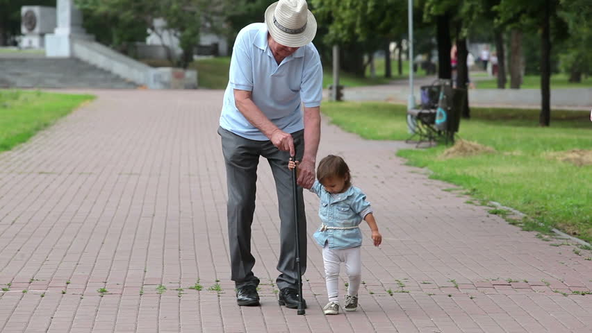 Granddaughter helping his grandfather to walk with a cane - HD stock video clip