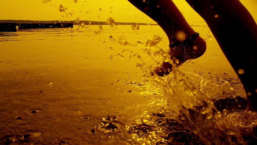 SLOW MOTION: Girl running in shallow water at sunset