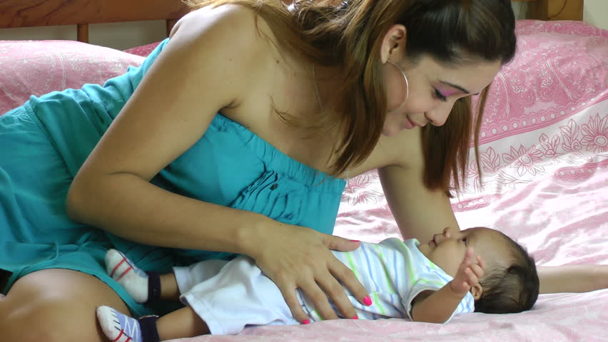 young Hispanic woman playing with her little baby in bed