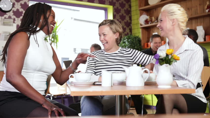 Group of multiethnic women enjoying cafe culture and relaxing over tea and coffee. A colourful and busy restaurant serving happy customers.