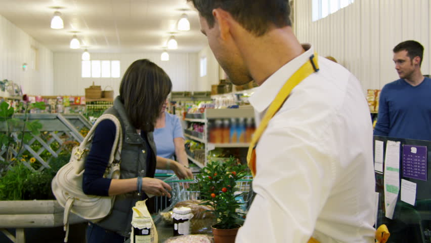 Customers buying food and staples from a cashier and paying at the till. Supermarket store.