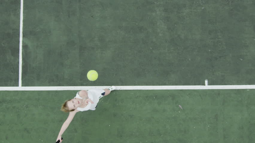 Tennis serve in slow motion from overhead angle.