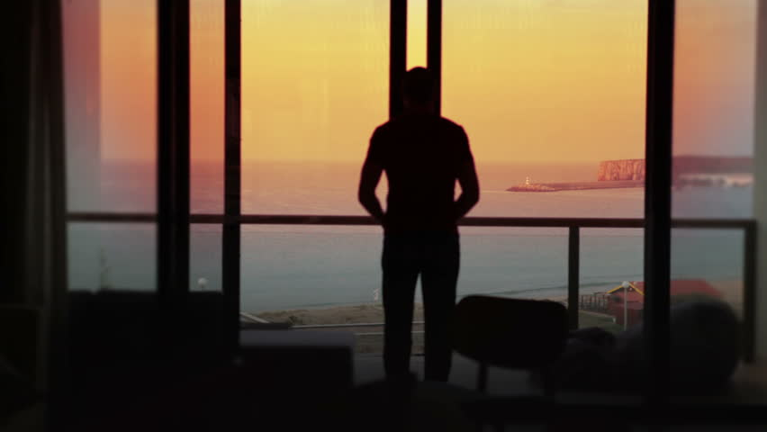 Man opens the doors to his terrace on holiday. Summer vacation at sunset.