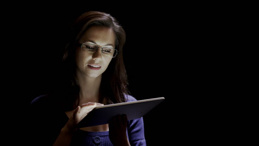 Attractive young woman using a tablet against a black background.