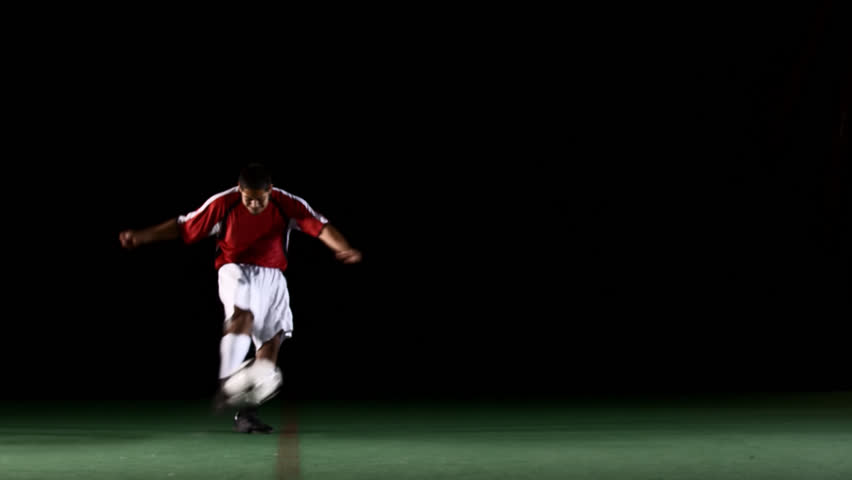 A soccer, or football, player that is dramatically and artistically lit, on an artificial field pitch on a black background, runs up and kicks the ball very hard and fast - HD stock video clip