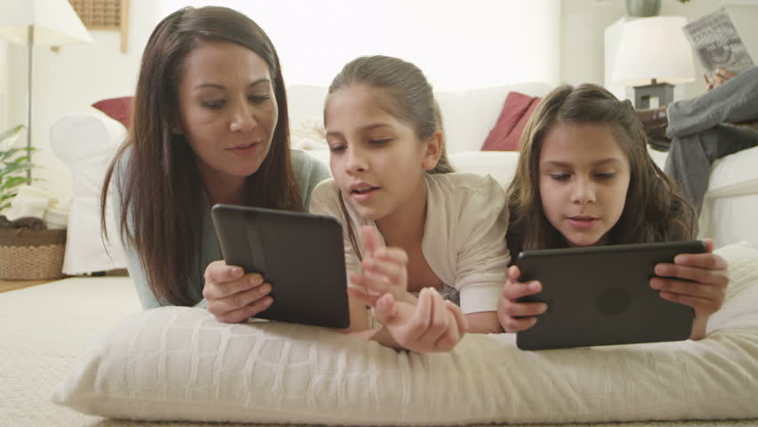 A mom lies with her daughters and plays with their digital tablets with them. Close up shot.