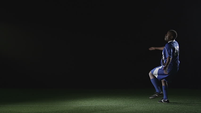 Soccer player jumps and side kicks the ball while in the air. Wide slow motion shot.