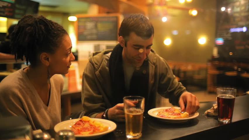 A good looking couple eat some pizza while on a date together. Medium shot.