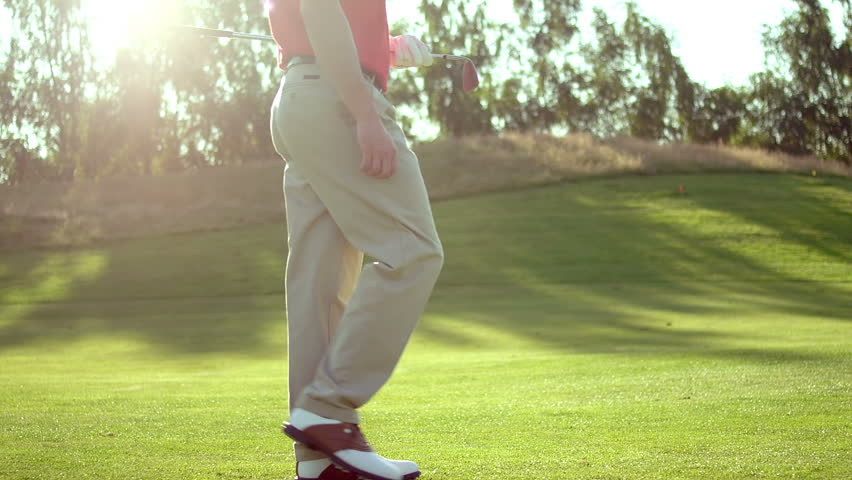 A male golfer walks through the frame while on the fairway. Medium slow motion shot.\xE6