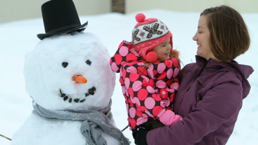 Mother and daughter building a snowman