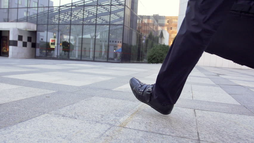 Slow Motion Rear View Shot Of A Male Legs Walking Through Business Area. Casually Dressed And Carrying A Briefcase.