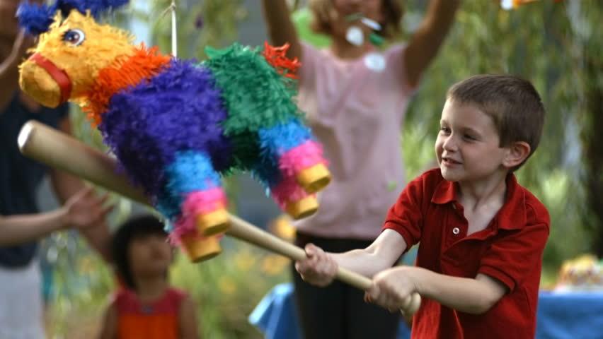 Boy hitting a pinata at party, slow motion