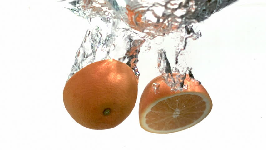 Oranges splash into water, slow motion