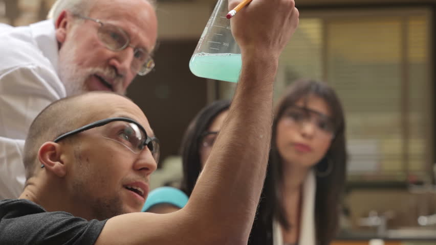 A college professor helps students understand a chemistry experiment