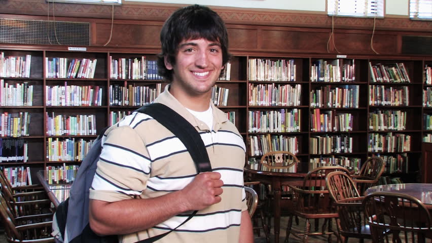 A confident student proudly looks at the camera and smiles. - HD stock video clip