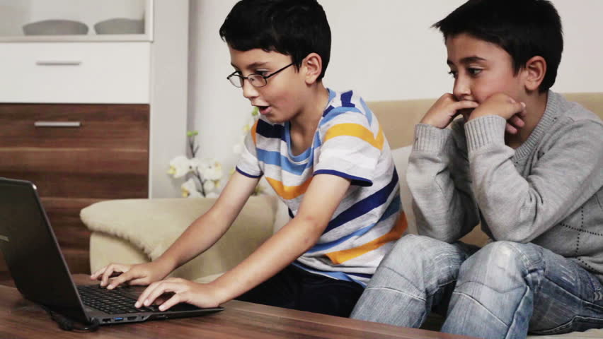 2 kids who are friends and brothers having fun playing on a laptop computer playing video games on a website and studying doing homework for school at home in the living room during the day