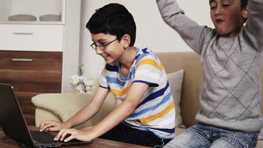 2 young boys having fun browsing the internet playing video games and doing homework on a laptop computer at home in the living room during the day