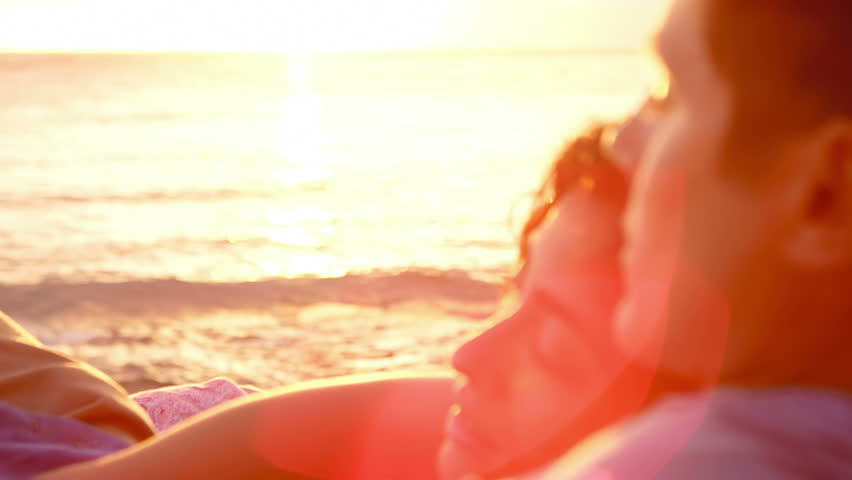A woman lays on a man's chest as they sit on the beach and watch the sun set together