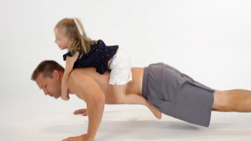 A young muscular father does a set of push-ups with his happy little daughter riding on his back.