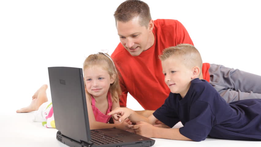 A dad on the floor with his little girl and young son, looking at something on the laptop. Dolly footage.   Shutterstock HD Video #480025