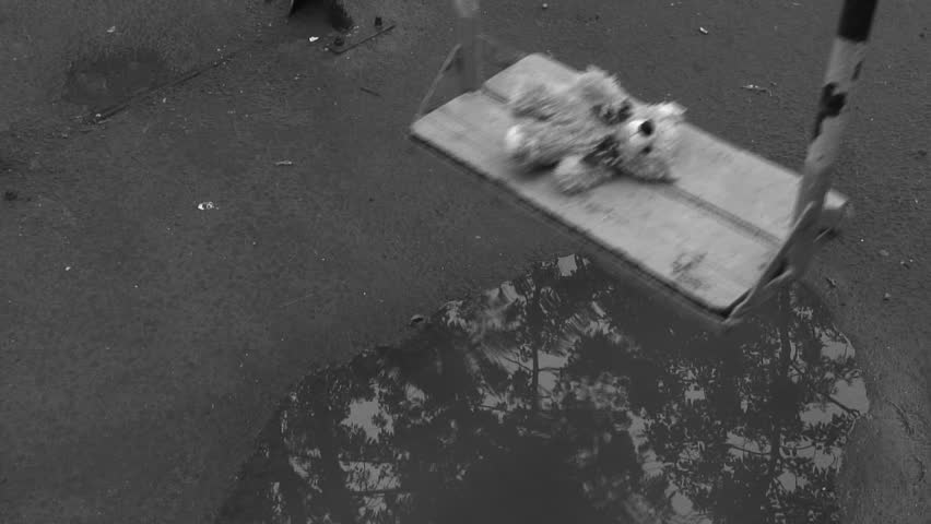 Forgotten Teddy bear on a swing under rain. Deep depression theme. Black and white. - HD stock footage clip