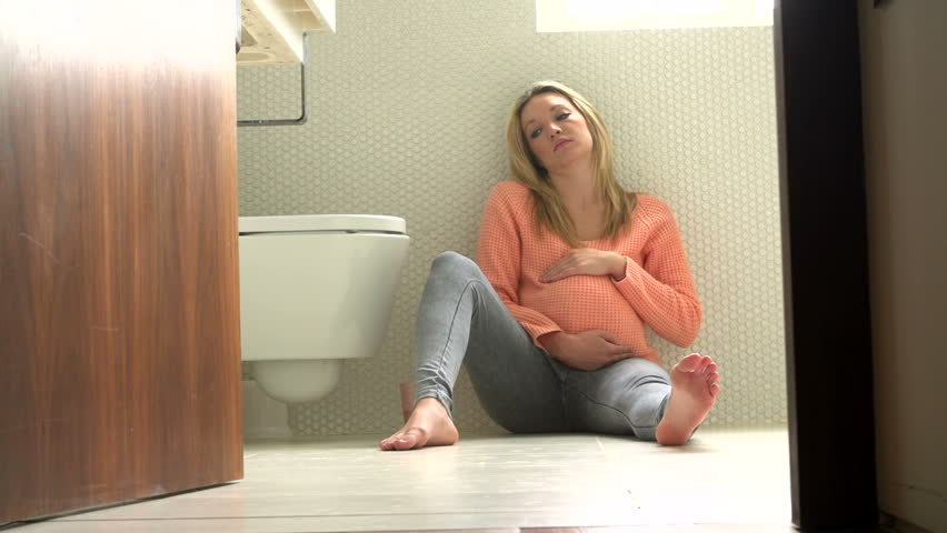 Nauseous pregnant teenage girl sits unhappily on the bathroom floor trying not to throw up