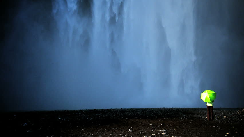 Concept shot of lone female standing on the edge of a waterfall with green umbrella to shelter from climate change 60 FPS - HD stock video clip