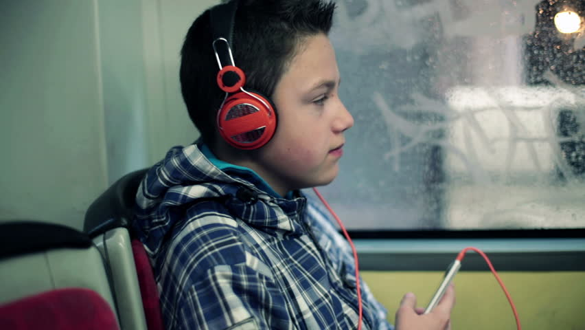 Young boy listen to the music on smartphone while riding bus