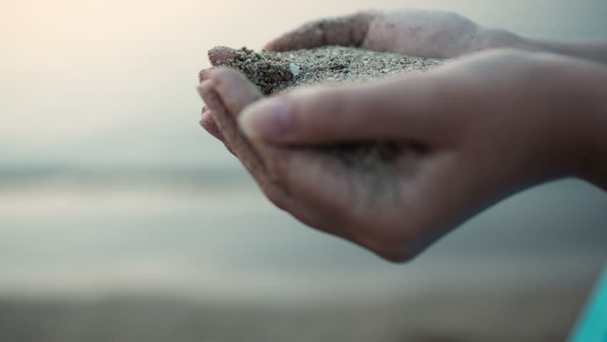 Close up view of sea sand running through a womans hands against a blurred ocean backdrop with copyspace conceptual of a summer vacation