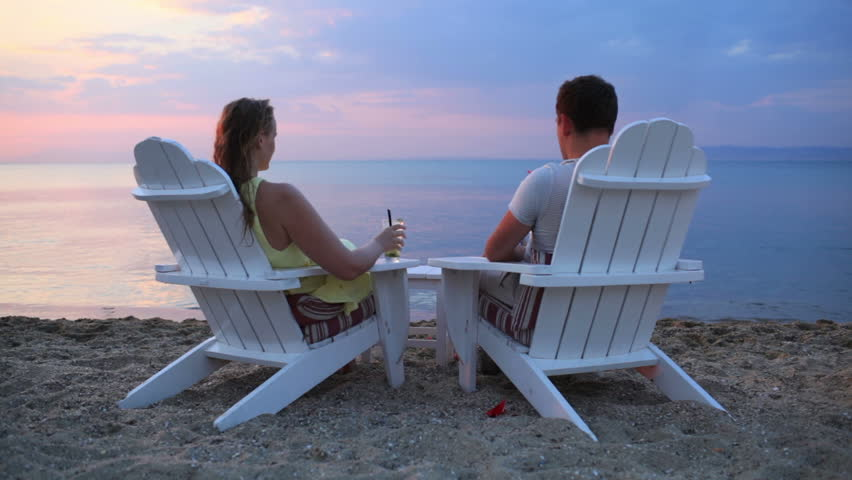 Romantic Pictures Of Tropical Beaches: Couple Sitting In Beach Chairs With Tropical Drinks Stock