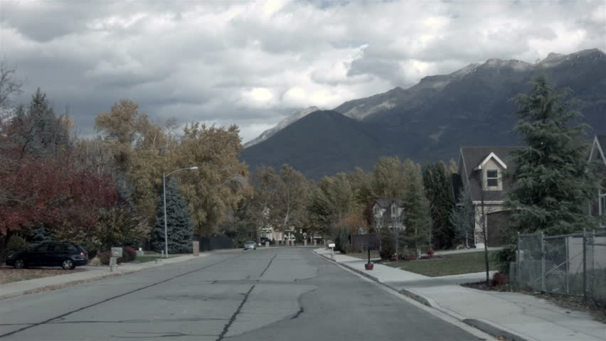 Driving through neighborhood homes POV HD. Driving through urban city busy and home area on public roads. Autumn colors on trees. Neighborhood part of town. Season change from summer to winter. - HD stock footage clip