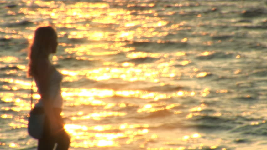 Lonely girl walks along beach and looks at horizon. - HD stock footage clip