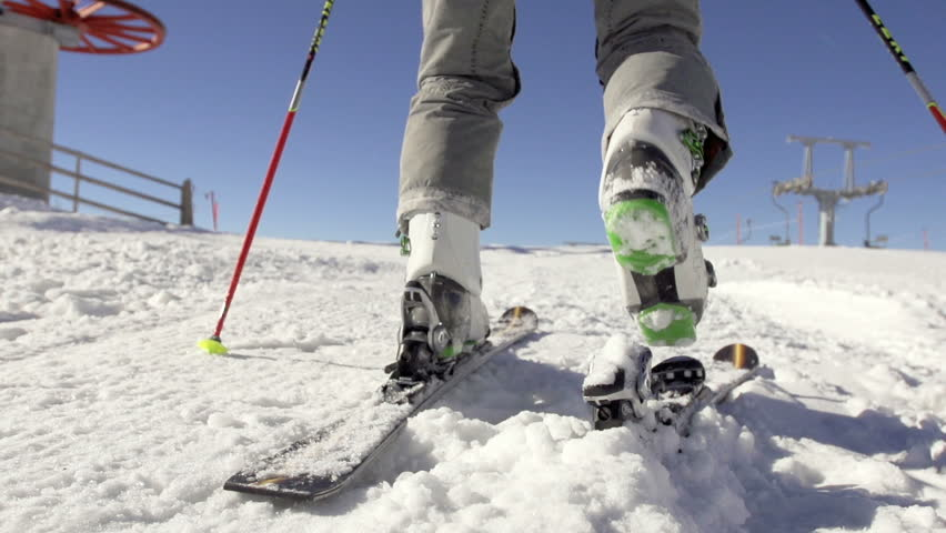 Slow motion rear shot of skier attaching his ski boots to
