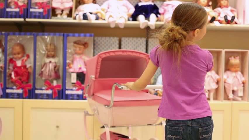 girl in a pink T-shirt toy stroller rolls on the background of shelves with toys - HD stock footage clip