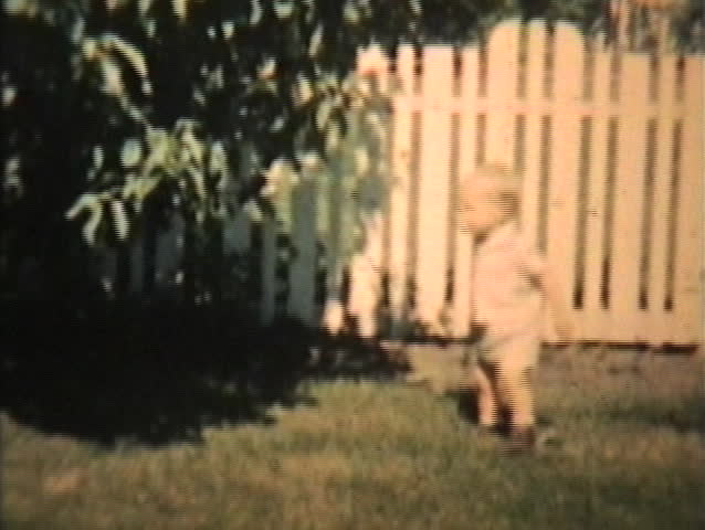 A little toddler plays with his Grandma in the back yard in 1963. (Vintage 8mm film footage).