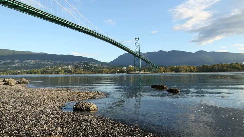 Burrard Inlet, Lions Gate Bridge, Vancouver Morning. Sport fishermen troll for salmon from their boats under the Lions Gate Bridge at dawn. British Columbia, Canada. Camera dolly move. - HD stock footage clip