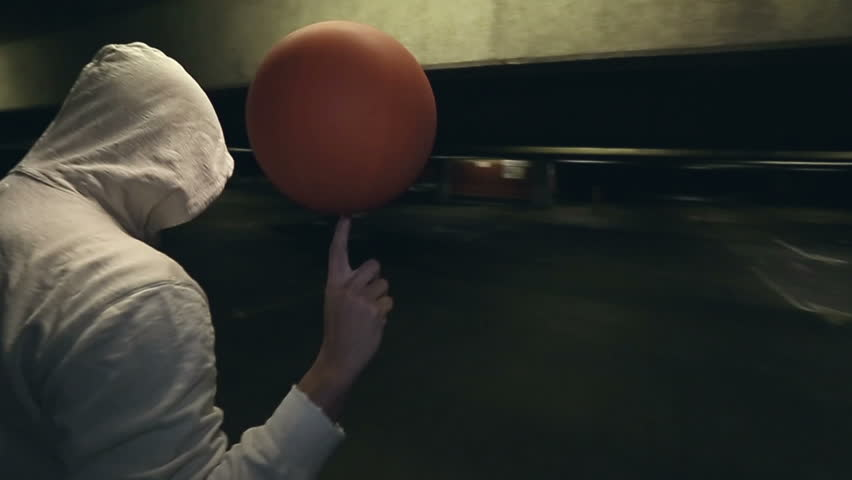 Hooded Street ball basketball player spinning the ball whilst the camera circles him - HD stock footage clip
