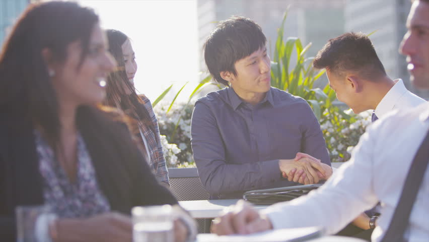 Cheerful young asian business team in a meeting on a busy open air city roof terrace. They shake hands on the completion of a deal. In slow motion.