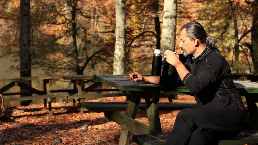 brunette man drinking a break time at forest