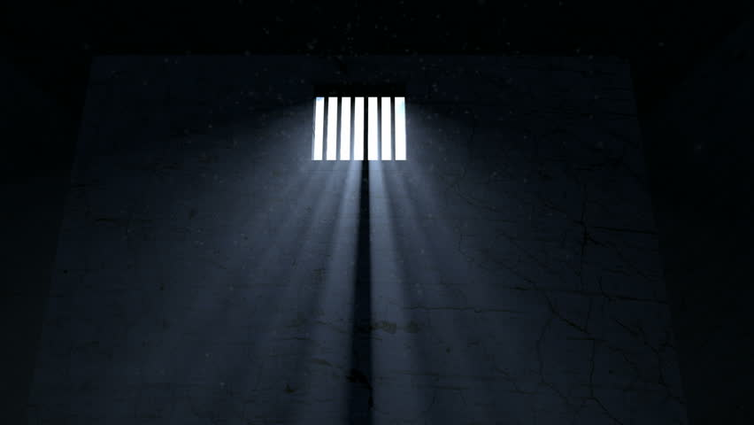 A slow pan of an empty dark jail cell with light rays penetrating a barred window  - HD stock video clip