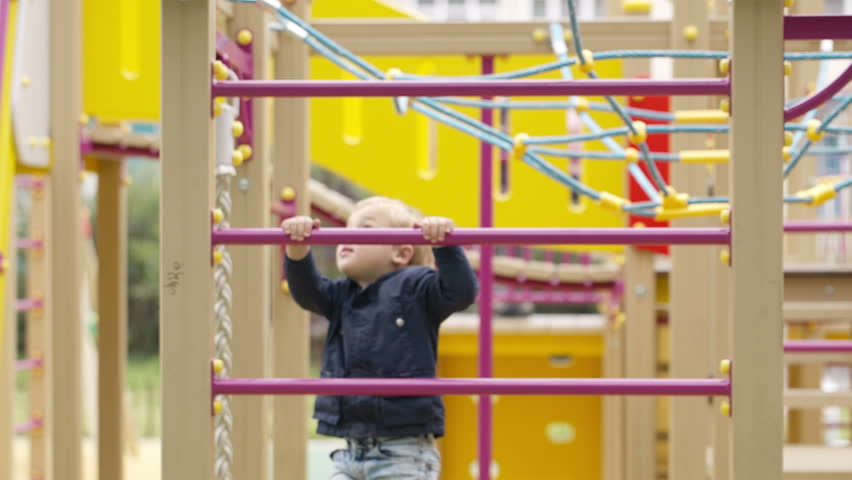 Cute little boy climbing on a the metal bars of a jungle gym in a childs playground - HD stock footage clip