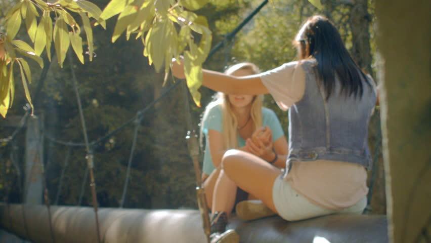 Teenage Girls Sitting, Talking  On A Walk Bridge In The Forest