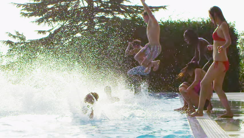 Happy fun loving group of friends jumping, splashing and playing in the swimming pool at a pool party. In slow motion. - HD stock video clip