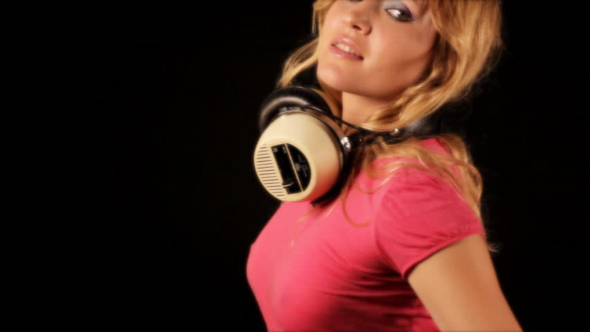 beautiful young blond woman dances in tight pink top and headphones - HD stock video clip