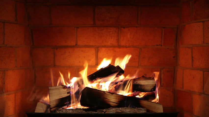 A Real Wood Fire Burning in a Clean Brick Fireplace.