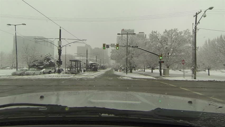 Urban road traffic business winter snow storm drive POV HD. Winter snow storm hit West and Midwest USA with extreme cold weather and snow. Dangerous driving conditions on snow packed and icy roads. - HD stock video clip