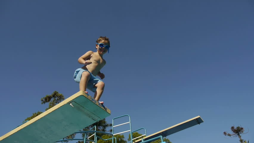 Boy jumping from springboard and diving in Swimming Pool -Slow Motion-